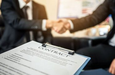 Close-up of business contract with pen at workplace on backgroun